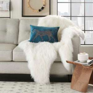 teal velvet pillow with gold leopard on faux fur which is on beige sofa